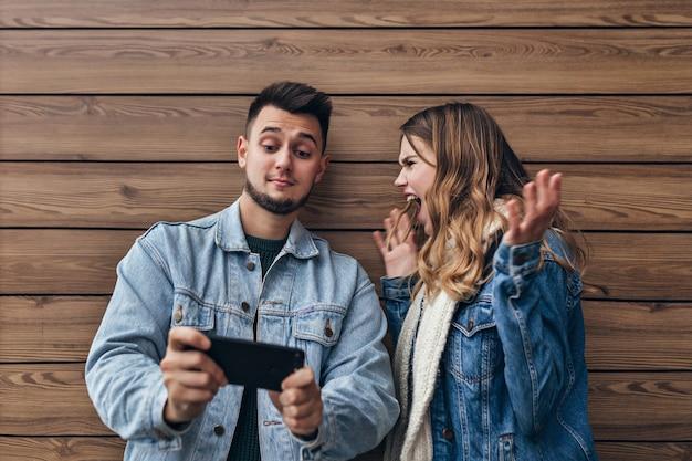 Ragazza sconvolta in giacca di jeans che grida all'uomo castana. ragazzo barbuto con lo smartphone nelle mani in piedi sulla parete in legno.