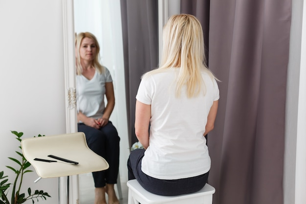 Расстроенная девушка перед зеркалом. женщина смотрит на свое отражение