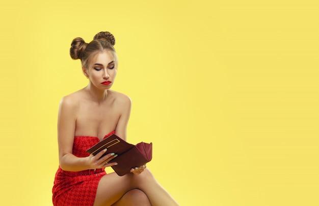 黄色の壁で分離されたショッピングの後悲しい顔で彼女の財布をチェックする赤いドレスで動揺の女の子