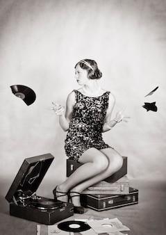 動揺した女の子が壊れた蓄音機のレコードの破片を散乱させる