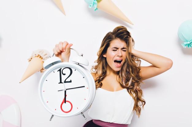 Расстроенная девушка кричит с закрытыми глазами, в панике трогает голову и держит большие белые часы. портрет несчастной молодой женщины в белой майке