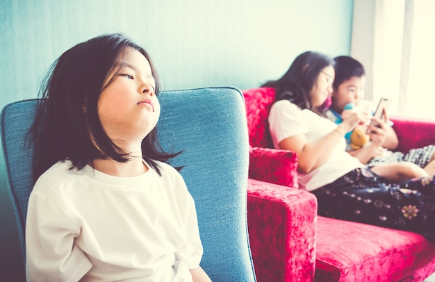 Upset girl sitting on chair mother enjoying with brother on sofa at home