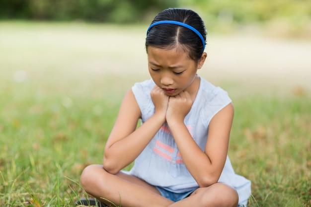 Расстроенная девушка сидит на траве