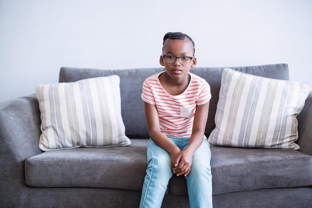 廊下のソファーに座っている動揺の女の子