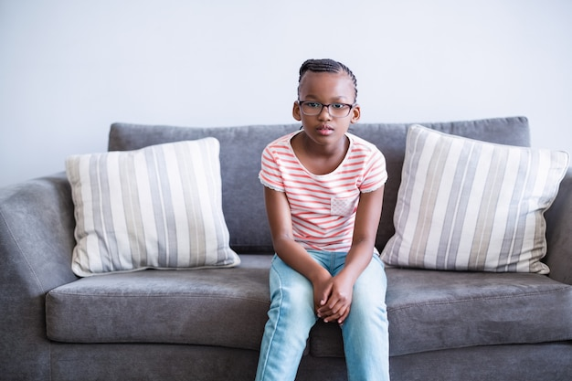 Upset girl sitting on sofa in corridor