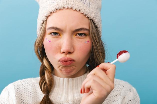 孤立して立っているセーターを着て、ロリポップを食べて動揺している女の子