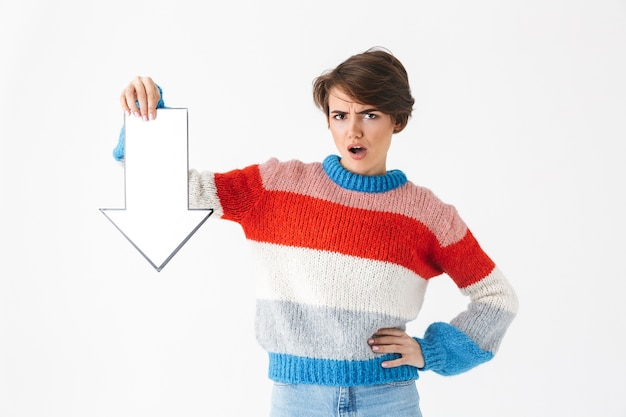 흰색에 고립 된 스웨터 서를 입고 화가 소녀, 종이 화살표로 아래쪽을 가리키는