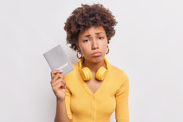 Upset gloomy afro american woman with curly hair holds passport feels unhappy as cannot travel during coronavirus pandemic wears wireless headphones around neck poses indoor