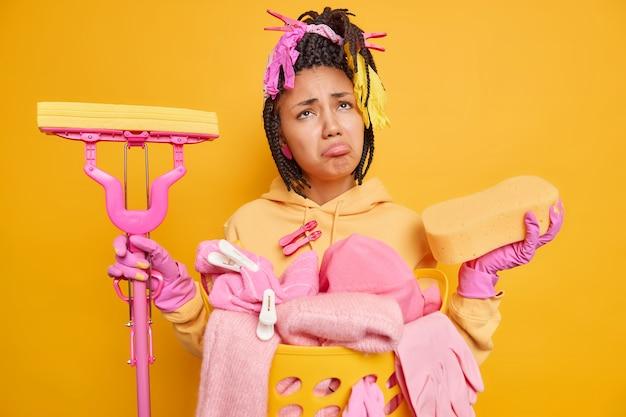 Upset gloomy afro american woman with dreadlocks holds sponge and mop