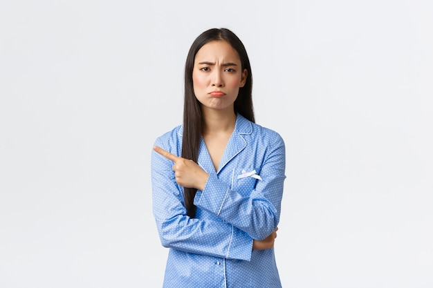 Upset gloomy asian girl in blue pajamas grimacing disappointed and sad, showing something bad, pointing finger left and pouting, complaining something unfair or saddening, standing white background.