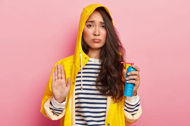 動揺した暗いアジアの女性は拒否のジェスチャーをします、いいえと言います、病気を避けるために医療スプレーを保持し、フード付きの防水黄色のレインコート、縞模様のジャンパーを着ています