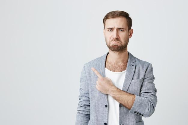 怒って悲観的なひげを生やした男がふくれっ面、左上隅を指す