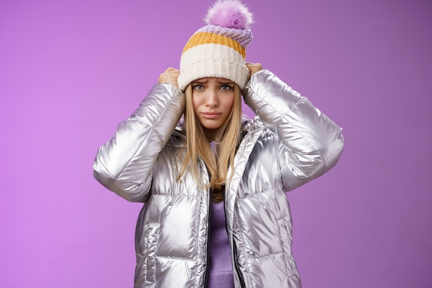 Upset gloomy complaining blond girlfriend whining standing upset disappointed sulking offended pulling hat forehead look offended unhappy wearing stylish glittering jacket unwilling go outside cold.