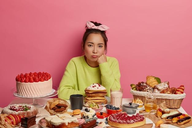 動揺した憂鬱な女性は、お菓子やお菓子を食べたいと思って、たくさんのデザートを添えてテーブルでポーズをとり、ダイエットを続け、ジャンクフードを避け、誘惑を感じます。
