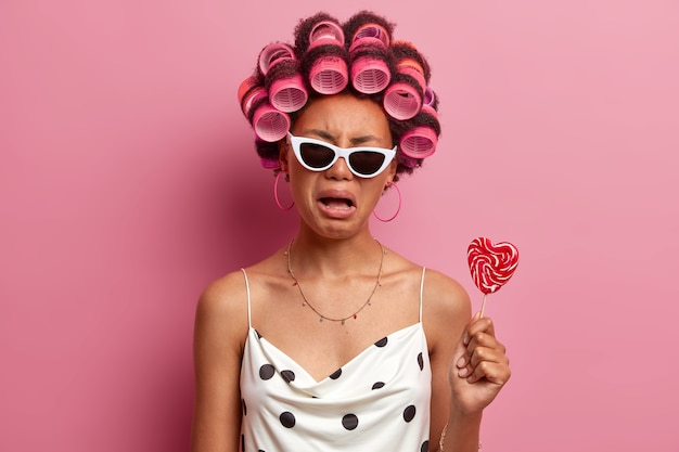 Upset gloomy woman wears hair curlers, cries with displeased expression, gets ready for holiday, makes hairstyle, poses with tasty candy on stick, wears sunglasses and casual dress