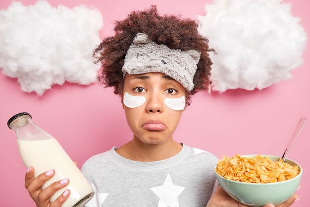 Upset good looking afro american woman has sleepy expression wakes up early in morning holds bowl of cereals and milk bottle wears slumber suit beauty patches under eyes isolated over pink wall