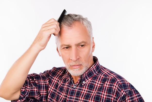 Расстроенный серый старик расчесывает волосы