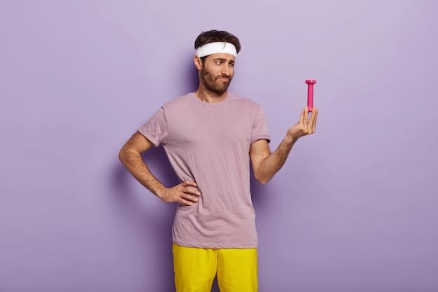 화가 난 남자는 손에 든 작은 덤벨을 무관심하고 너무 가볍다 고 생각하고 머리띠를 착용합니다.