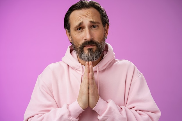 Upset handsome bearded mature man need help asking forgiveness supplicating press palms together praying frowning sorrow begging favour lend money, standing purple background miserable.