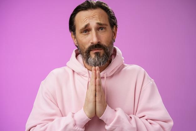 화난 잘 생긴 수염 난 성숙한 남자는 용서를 구걸하는 데 도움이 필요합니다.