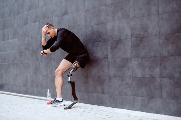 Upset handsome caucasian sportsman with artificial leg leaning on the wall, holding head and looking at wristwatch.