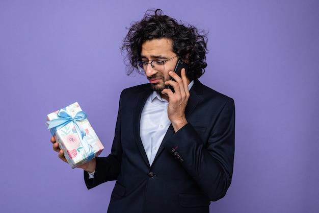 3월 8일 국제 여성의 날을 축하하는 슬픈 표정으로 보라색 배경 위에 서서 휴대폰으로 통화하는 선물을 들고 있는 화난 잘생긴 남자