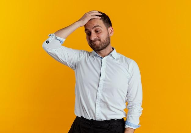 Uomo bello sconvolto mette la mano sulla fronte guardando in basso isolato sulla parete arancione