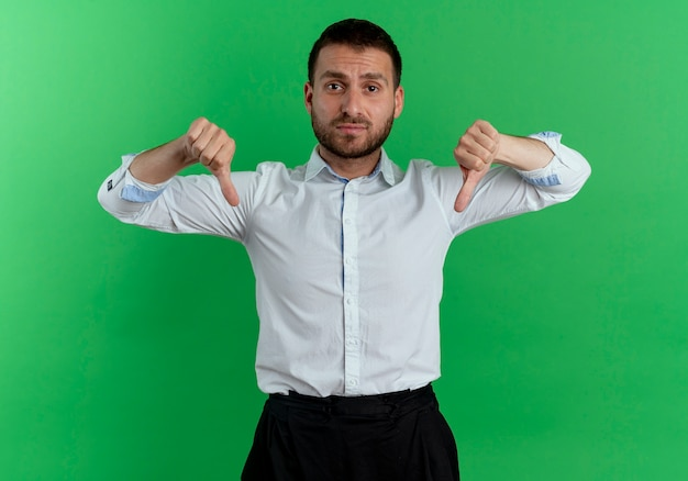 Upset handsome man thumbs down with two hands isolated on green wall