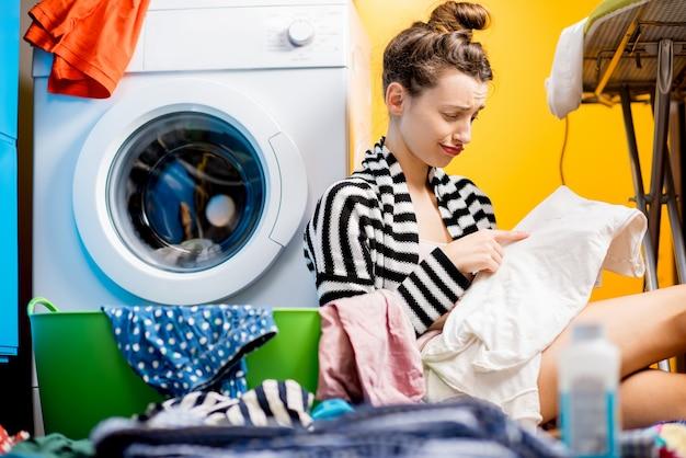 Расстроенная домохозяйка смотрит на грязную одежду, сидя возле стиральной машины дома