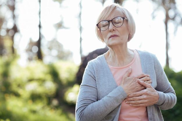 Расстроенная больная слабая женщина трогает свою грудь и чувствует боль, сидя на открытом воздухе
