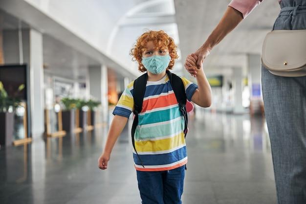 Расстроенный ребенок с рюкзаком, держащим руку
