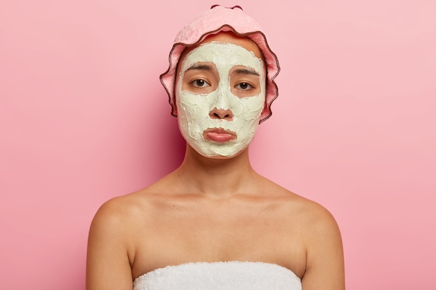 Upset korean young female has dissatisfied sad look, gets beauty treatment, unhappy to have wrinkles and problematic skin, has cosmetic mask on face, wears waterproof headgear for taking shower