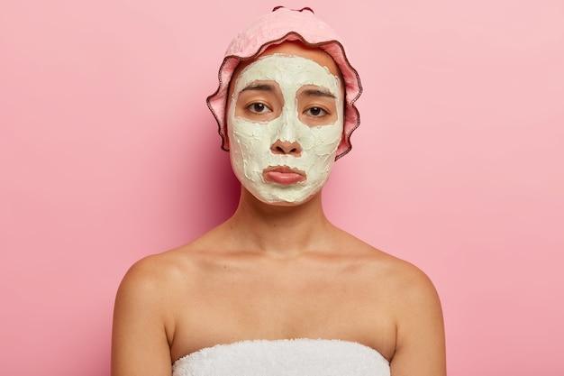 화난 한국의 젊은 여성은 슬픈 표정이 불만족스럽고, 미용 치료를 받고, 주름과 문제가있는 피부가 불행하며, 얼굴에 미용 마스크를 쓰고, 샤워를 할 때 방수 모자를 쓰고 있습니다.