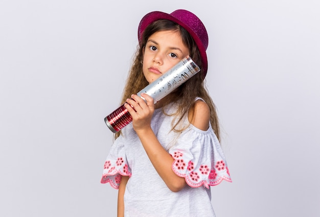 Upset little caucasian girl with purple party hat holding confetti cannon isolated on white wall with copy space