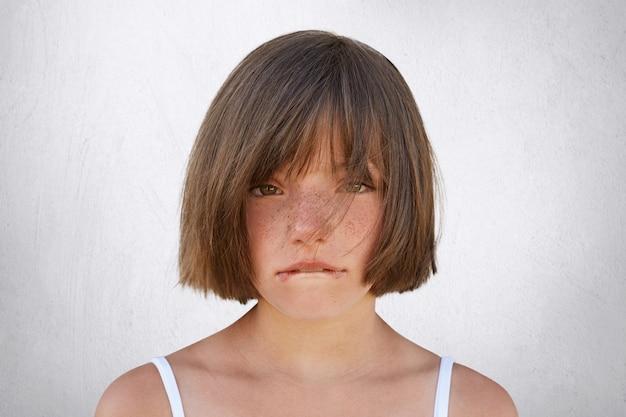 Bambina turbata che ha litigio con i suoi genitori, esaminante innocentemente nella macchina fotografica mentre curvando le sue labbra isolate su bianco. bambina sorridente che piange, mordendosi il labbro inferiore
