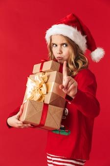 Расстроенная маленькая девочка в рождественском костюме стоит изолированно, держа подарочные коробки