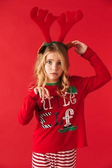 Расстроенная маленькая девочка в костюме рождественского оленя стоя изолирована