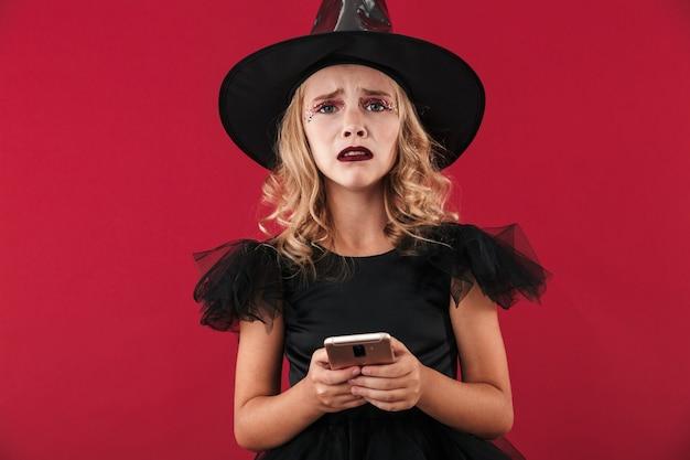 Upset little girl wearing halloween witch costume standing