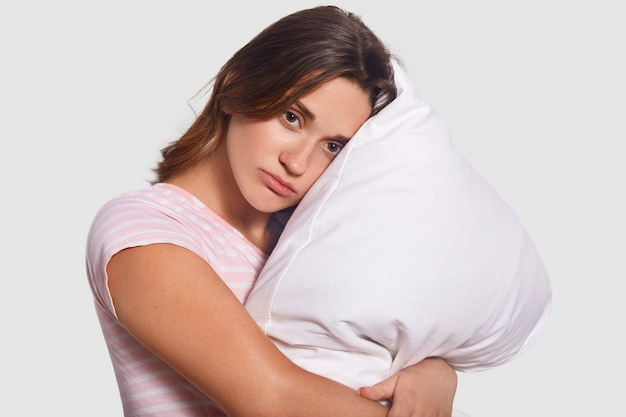 Upset lonely female embraces white pillow, looks with upset expression, thinks about something before falling asleep, dressed in casual clothes, isolated on studio wall. people and sleep concept