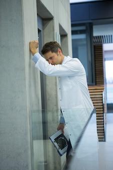 Upset male doctor standing near corridor
