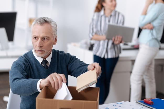 物を集めて、考えを深くしながら職場に座っている男性の動揺