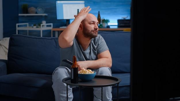 Расстроенный футбольный болельщик смотрит спортивную игру в поддержку любимой команды, ест попкорн нервной кормы ...