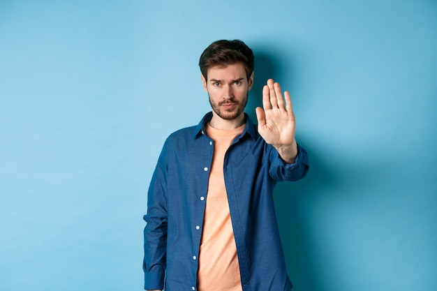 Upset man frowning and asking to stop, stretch out hand to prohibit or disagree with something bad, standing on blue background.
