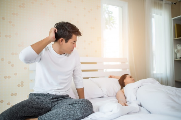 Upset man having problem sitting on the bed after arguing with his girlfriend