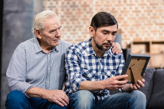 Upset man holding a photo frame while his father supporting him at home