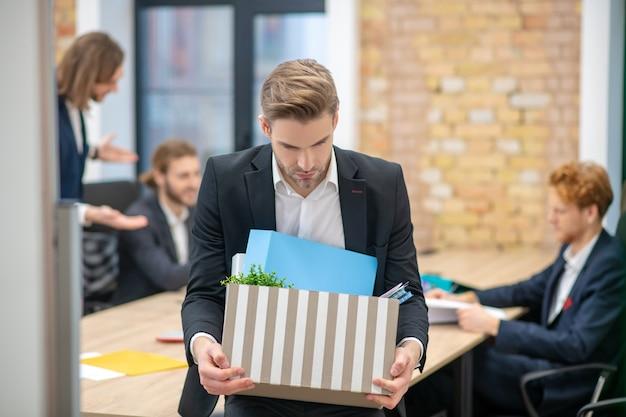 暗いスーツと白いシャツを着た動揺した男と物の箱と同僚がオフィスの後ろで通信している