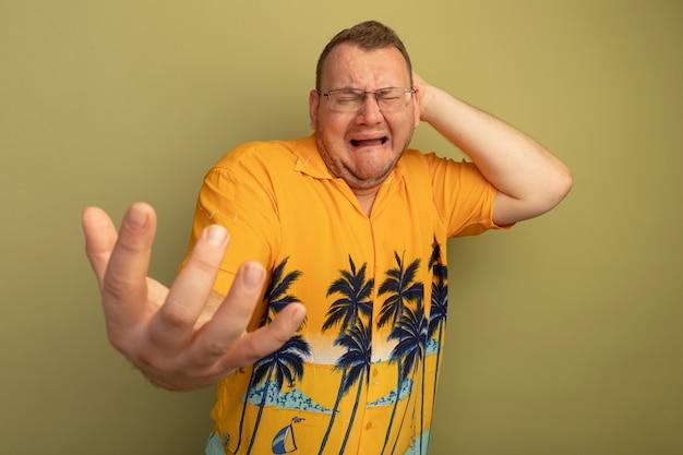 明るい壁の上に立って腕を伸ばして激しく泣いているオレンジ色のシャツを着た眼鏡をかけた動揺した男