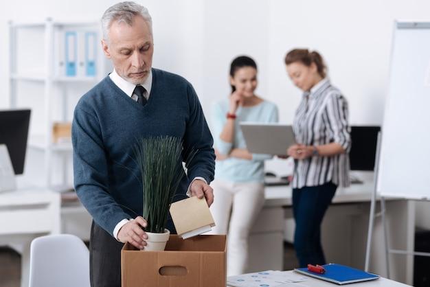 物を集めている間彼の職場の近くに立っている青いカーディガンを身に着けている年の動揺した男