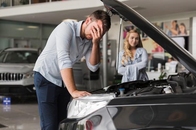 Расстроенный человек осматривает двигатель автомобиля