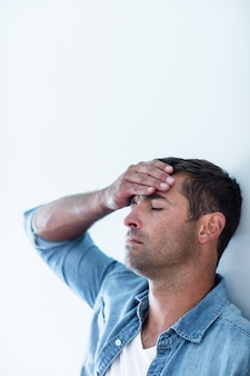 Upset man leaning on wall